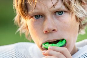 Boy playing football with custom mouthguard