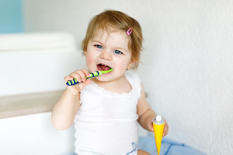 Little Baby Girl Holding Toothbrush